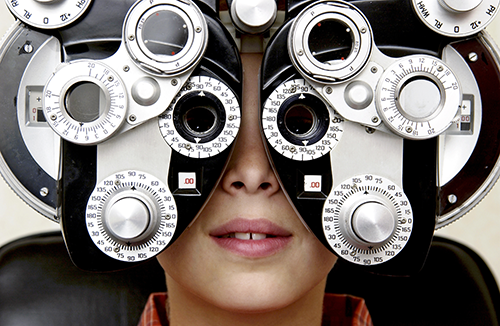 routine eye exam | photo of young boy getting an eye exam