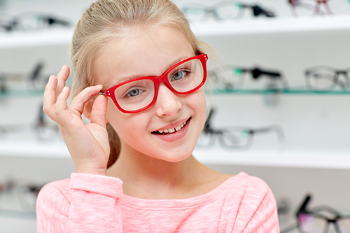 school eye exam | photo of young girl trying on red glasses