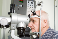 dilated eye exam | photo of oldr gentleman getting an eye exam