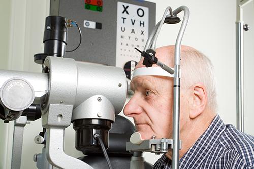 dilated eye exam | photo of oldr gentleman getting an eye exam